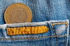 Pièce de monnaie turque avec une dénomination de 1 Lire dans la poche de vieux jeans de denim de biege Photo libre de droits