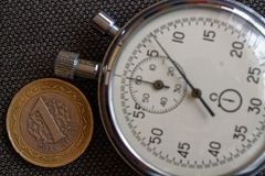 Pièce de monnaie turque avec une dénomination de 1 Lire et chronomètre sur le contexte de denim de beown - fond d'affaires Images stock