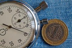 Pièce de monnaie turque avec une dénomination de 1 Lire et chronomètre sur le vieux contexte bleu de denim - fond d'affaires Photos stock