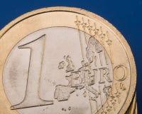 Pièce de monnaie un euro sur un fond bleu encaissez l'euro corde de note d'argent de l'orientation cent des euro cinq closeup Photos stock