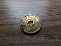 Pièce de monnaie de 5 Yens japonais dans ma main Image libre de droits