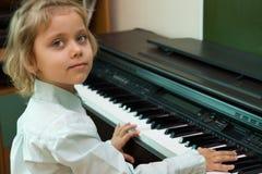 Pièce de petite fille sur un piano électrique Photos libres de droits
