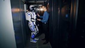 Pièce de serveur avec un robot placé par un ingénieur avec un ordinateur banque de vidéos