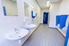 Pièce de toilette pour les hommes avec des éviers et des miroirs d'urinoirs Photographie stock