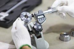 Pièce des véhicules à moteur d'inspection d'opérateur par micromètre Photos stock