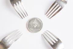 Pièce en argent cryptocurreny d'Ethereum placée entre les fourchettes sur le fond blanc, fourchette dure images stock