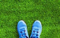 Pièce les espadrilles de sports de bleu sur l'herbe verte texturisée Photo libre de droits