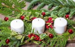 Pièce maîtresse à feuilles persistantes de Noël avec des bougies Image stock