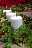 Pièce maîtresse à feuilles persistantes de Noël avec les bougies et le poinsetti blancs Photographie stock libre de droits