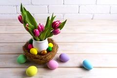 Pièce maîtresse de table de Pâques avec les oeufs peints à la main dans le nid Photographie stock