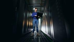 Pièce sombre de serveur avec un ingénieur support informatique regardant les unités banque de vidéos