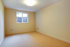 Pièce vide avec le tapis beige et la petite fenêtre de sous-sol. photographie stock libre de droits