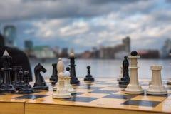 Pièces d'échecs blanches et noires de jeu de partie sur des agains d'un conseil en bois Photos stock