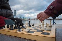 Pièces d'échecs blanches et noires de jeu de partie sur des agains d'un conseil en bois Photo stock