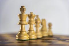 Pièces d'échecs dans une ligne, partie d'échecs sur le fond blanc Photos libres de droits