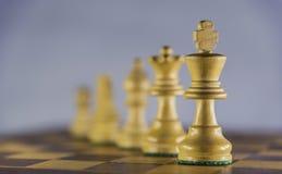 Pièces d'échecs dans une ligne, partie d'échecs sur le fond blanc Photo stock