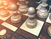 Pièces d'échecs en bois blanches sur un échiquier, modifié la tonalité avec la lumière du soleil Photographie stock libre de droits