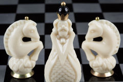 Pièces d'échecs en verre sur un échiquier Photographie stock libre de droits