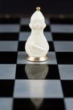 Pièces d'échecs en verre sur un échiquier Photographie stock