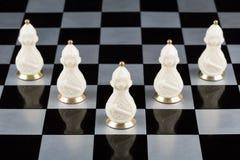Pièces d'échecs en verre sur un échiquier Image stock