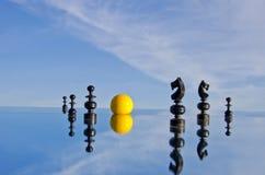 Pièces d'échecs noires et boule de billards jaune sur le miroir Images stock