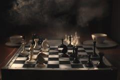 Pièces d'échecs sur l'échiquier Fond et fumée foncés photo stock