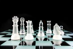 Pièces d'échecs sur un panneau de verre Photographie stock