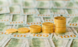 Pièces d'or empilées sur la nouvelle conception 100 billets d'un dollar Images libres de droits