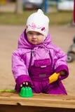 Pièces d'enfant dans le bac à sable Photo stock
