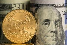 Pièces d'or pures devant des rouleaux de banque de devise des USA image libre de droits