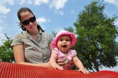 Pièces de bébé avec la momie dans la cour de jeu Photographie stock