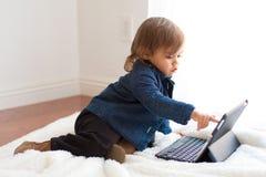 Pièces de fille d'enfant en bas âge avec le carnet d'iPad photographie stock