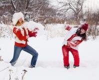 Pièces de filles avec la neige Photographie stock libre de droits