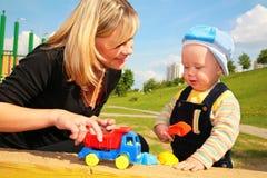 Pièces de mère avec l'enfant avec le véhicule de jouet Photographie stock