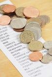 Pièces de monnaie britanniques et un reçu d'achats Image libre de droits