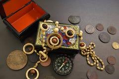 Pièces de monnaie, cercueil, perles et boussole antiques photo stock