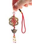 Pièces de monnaie chinoises antiques tenues dans la main avec les chaînes de caractères rouges. Photo stock