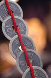 Pièces de monnaie chinoises sur la chaîne de caractères Photographie stock