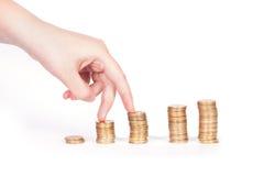 Pièces de monnaie colonne et doigts photo stock