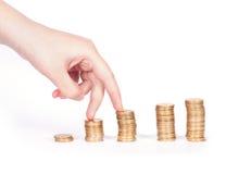 Pièces de monnaie colonne et doigts Photos stock