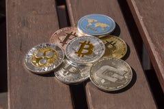 Pièces de monnaie de Cryptocurrency au-dessus d'une table en bois ; Bitcoin, ondulation, tiret Image stock