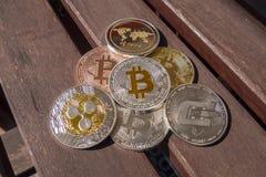 Pièces de monnaie de Cryptocurrency au-dessus d'une table en bois ; Bitcoin, ondulation, tiret Images libres de droits