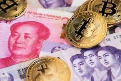 Pièces de monnaie de cryptocurrency de Bitcoin sur la devise de la Chine Yuan Renminbi et les billets de banque gagnés coréens du photo libre de droits
