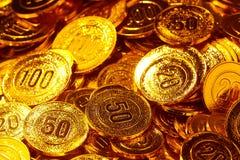 Pièces de monnaie d'or empilées dans un tas de fond Photos stock