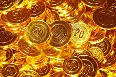 Pièces de monnaie d'or empilées dans un tas de fond Images stock
