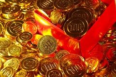 Pièces de monnaie d'or empilées dans un tas et dans une boîte de fond Photos stock