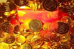 Pièces de monnaie d'or empilées dans un tas et dans une boîte de fond Photographie stock libre de droits