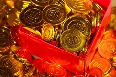 Pièces de monnaie d'or empilées dans un tas et dans une boîte de fond Images libres de droits