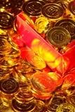 Pièces de monnaie d'or empilées dans un tas et dans une boîte de fond Photo stock