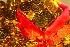 Pièces de monnaie d'or empilées dans un tas et dans une boîte de fond Réserves d'or Image stock